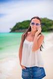 Młoda piękna kobieta opowiada jej smartphone przy plażą Zdjęcia Stock