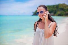 Młoda piękna kobieta opowiada jej telefonem przy plażą Fotografia Stock
