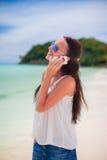 Młoda piękna kobieta opowiada jej telefonem przy plażą Zdjęcie Royalty Free