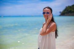 Młoda piękna kobieta opowiada na ona przy plażą Obrazy Royalty Free