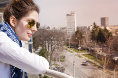 Młoda Piękna kobieta patrzeje ulicę od balkonu Obraz Royalty Free