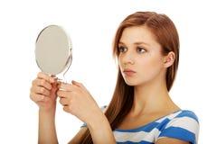 Młoda piękna kobieta patrzeje w lustrze zdjęcia stock