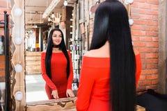 Młoda piękna kobieta patrzeje w lustrze w czerwieni sukni obrazy stock