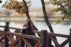 Młoda piękna kobieta pije herbacianego pobliskiego jezioro w ciepłym klasycznym żakiecie Fotografia Royalty Free