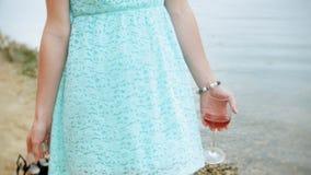 Młoda piękna kobieta pije wino od szkła i odprowadzenie wzdłuż piaskowatej plaży morze zbiory