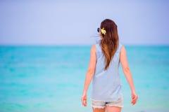 Młoda piękna kobieta podczas tropikalnego plaża wakacje Cieszy się suumer urlopowego na plaży przy Afryka z frangipani samotnie Obrazy Royalty Free