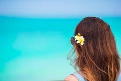 Młoda piękna kobieta podczas tropikalnego plaża wakacje Cieszy się suumer urlopowego na plaży z frangipani kwiatami samotnie Obraz Royalty Free