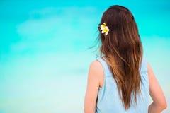 Młoda piękna kobieta podczas tropikalnego plaża wakacje Cieszy się suumer urlopowego na plaży z frangipani kwiatami samotnie Zdjęcia Royalty Free