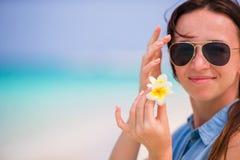 Młoda piękna kobieta podczas tropikalnego plaża wakacje Cieszy się suumer urlopowego na plaży z frangipani kwiatami samotnie Fotografia Royalty Free
