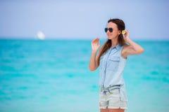 Młoda piękna kobieta podczas tropikalnego plaża wakacje Cieszy się suumer urlopowego na plaży z frangipani kwiatami samotnie Zdjęcie Royalty Free