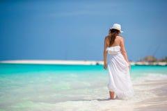 Młoda piękna kobieta podczas tropikalnego plaża wakacje Cieszy się wakacje samotnie na plaży z frangipani kwiatami Zdjęcie Royalty Free
