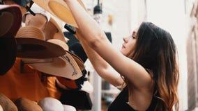 Młoda piękna kobieta próbuje na kapeluszach w ulica sklepie Atrakcyjna kobieta iść robić zakupy w śródmieściu zdjęcie wideo