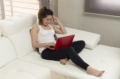 Młoda piękna kobieta pracuje na kanapie używać laptop w domu Obrazy Stock