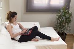 Młoda piękna kobieta pracuje na kanapie używać laptop w domu Obrazy Royalty Free