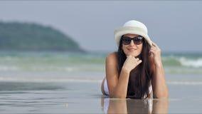 Młoda piękna kobieta relaksuje i sunbathing przy tropikalną plażą w okularach przeciwsłonecznych zdjęcie wideo