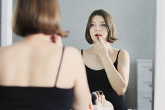Młoda piękna kobieta robi makeup i patrzeje w lustrze Fotografia Royalty Free