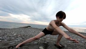 Młoda piękna kobieta robi rozciągania ćwiczeniu przy seashore Zdrowy Styl ?ycia koncepcja kulowego fitness pilates z?agodzenie fi zdjęcie wideo