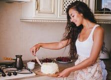 Młoda piękna kobieta robi tortowi przy kuchnią Zdjęcie Royalty Free
