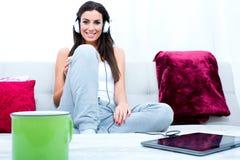 Młoda piękna kobieta słucha muzyka z pastylka pecetem przy hom Zdjęcia Stock