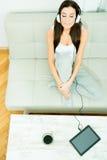 Młoda piękna kobieta słucha muzyka z pastylka pecetem przy hom Fotografia Royalty Free