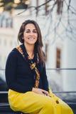 Młoda piękna kobieta siedzi na ulicie na ławce przy zmierzchem Portret uśmiechnięta dziewczyna w żółtej spódnicie, nowożytny snea Obrazy Stock