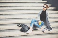 Młoda piękna kobieta, siedzi na ulicie zdjęcia stock