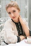 Młoda piękna kobieta siedzi przy stołem Fotografia Royalty Free