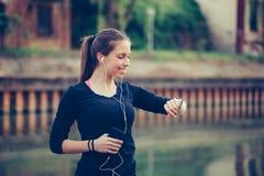 Młoda piękna kobieta sprawdza sprawność fizyczna postęp na jej mądrze zegarku zdjęcie stock