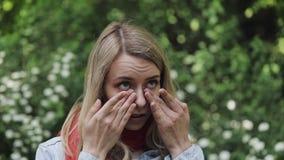 Młoda piękna kobieta stoi przeciw tłu kwiatonośni drzewa naciera ona oczy Alergia, rhinitis, oko choroby zdjęcie wideo