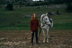 Młoda piękna kobieta trzyma konia, natura, góry, wzgórza Zdjęcie Stock