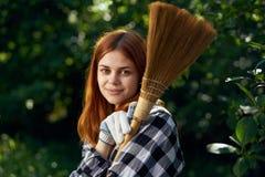 Młoda piękna kobieta trzyma miotłę, ogrodnictwo, ogrodniczka, lato Obrazy Stock