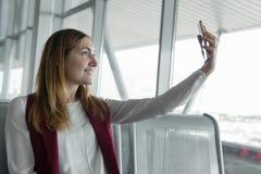Młoda piękna kobieta uśmiecha się selfie w lotniskowym terminal i robi fotografia royalty free