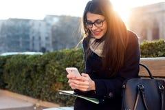 Młoda piękna kobieta używa jej telefon komórkowego w ulicie Zdjęcie Stock