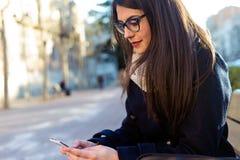 Młoda piękna kobieta używa jej telefon komórkowego w ulicie Obrazy Stock