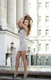Młoda piękna kobieta w beżu skrótu smokingowy pozować outdoors w su Obraz Stock