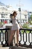 Młoda piękna kobieta w beżu skrótu smokingowy pozować outdoors w su Zdjęcia Stock