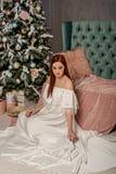 Młoda piękna kobieta w białym eleganckim wieczór sukni obsiadaniu na podłogowej pobliskiej choince i teraźniejszość Wnętrze z boż obraz stock