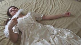 Młoda piękna kobieta w białym rocznik balowej sukni lying on the beach na ogromnym złotym łóżku i falowanie z piórkowym fan zbiory wideo