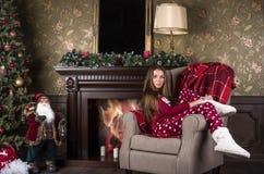 Młoda piękna kobieta w czerwonych bożych narodzeniach stwarza ognisko domowe odzieżowe piżamy i bielu domu buty siedzą w krześle  obraz stock