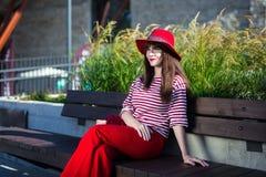 Młoda piękna kobieta w czerwonym obsiadaniu w miasto parku Obrazy Royalty Free