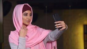 Młoda piękna kobieta w hijab robi selfie na telefon komórkowy kamerze Muzułmańska kobieta i nowożytna technologia Obrazy Royalty Free