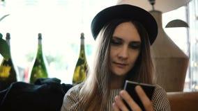 Młoda piękna kobieta w kapeluszowym obsiadaniu w restauraci i używać smartphone, surfuje internet podczas gdy czekający rozkaz zbiory