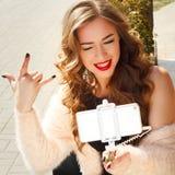 Młoda piękna kobieta w kapeluszu robi selfie outdoors pokazuje skałę Zdjęcia Stock
