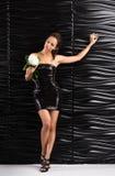 Młoda piękna kobieta w krótkim czerni smokingowym pozujący z białym kwiatem w ona rękę Fotografia Stock
