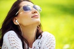 Młoda piękna kobieta w lato parku cieszy się muzykę Obraz Stock