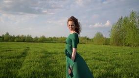 Młoda piękna kobieta w pięknej sukni stoi w polu przy zmierzchem zbiory