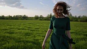 Młoda piękna kobieta w pięknym smokingowym odprowadzeniu wokoło pola przy zmierzchem zbiory