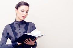 Młoda piękna kobieta w rocznik sukni czytelniczej biblii Zdjęcie Stock
