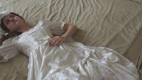 Młoda piękna kobieta w rocznika balowym kostiumowym lying on the beach na ogromnym złotym główkowaniu i łóżku podczas gdy machają zbiory wideo