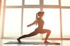 Młoda piękna kobieta w rzeczywistość wirtualna szkłach robi aerobikom daleko Przyszłościowy technologii pojęcie Nowożytny zobrazo Obraz Royalty Free